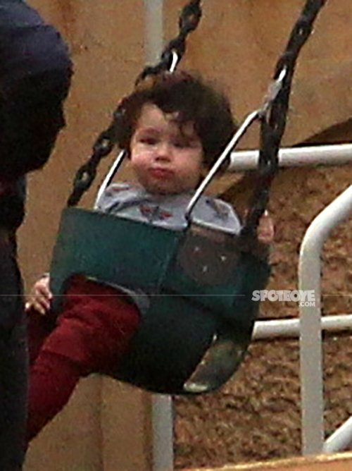 taimur ali khan looks straight to the cameras as they click his pictures on the swing