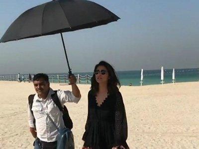 parineeti chopra makes another person carry an umbrella for her on a beach in dubai