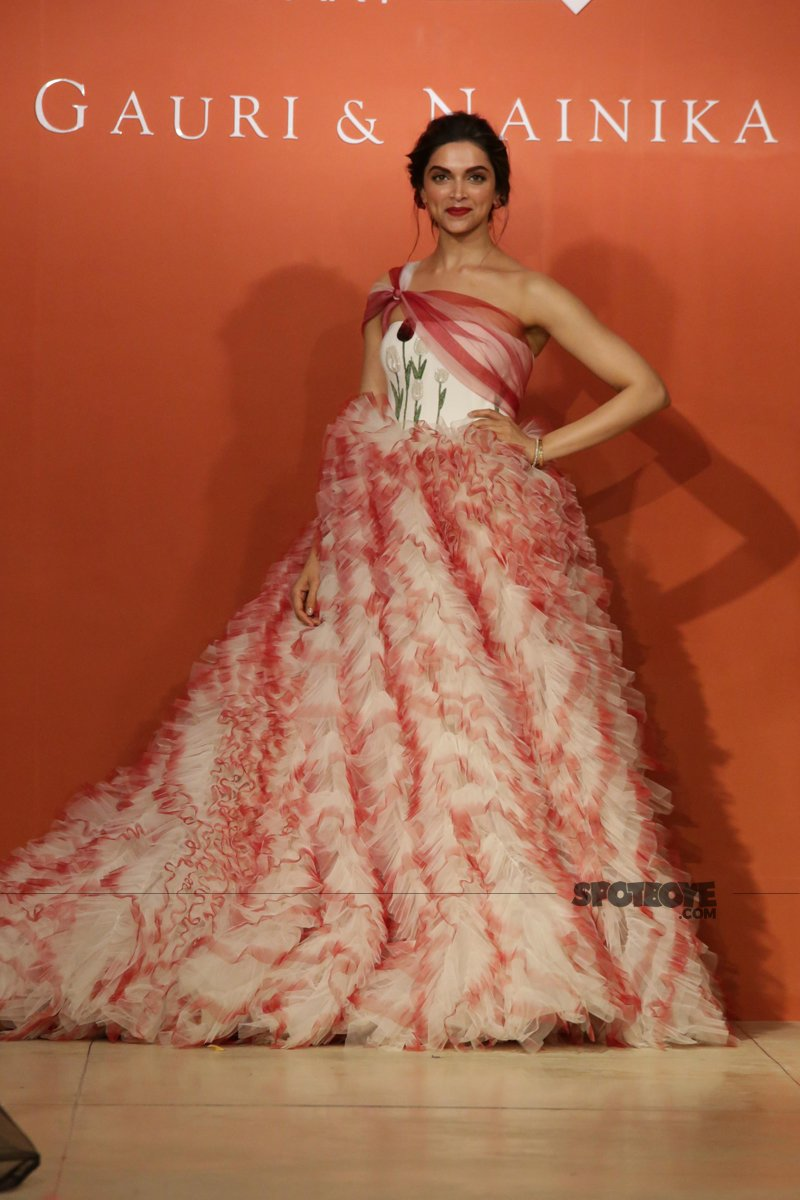deepika padukone posing for the shutterbugs donned in red and white carnation