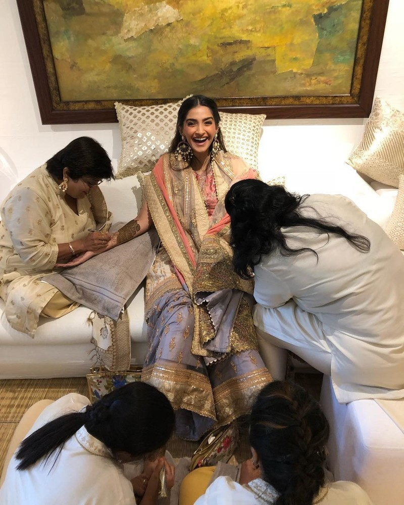 sonam kapoor s poses for a picture while applying mehendi